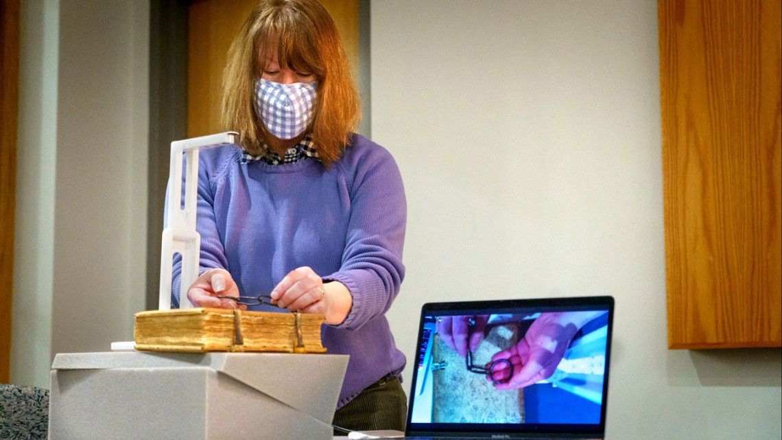 Julia Gardner, head of research services for the library's Division of Rare and Manuscript Collections, uses an overhead document camera to show a 15th-century book of sermons, originally attached to a lectern by a chain.