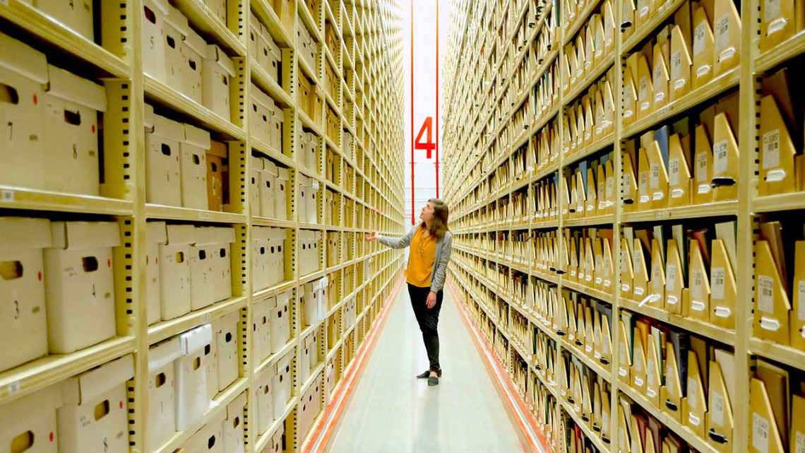 Phoebe Kowalewski, curator of The Atlantic Philanthropies archives, walks the aisles of the Library Annex, where 2,000 cubic feet of the foundation's physical archival materials are kept.