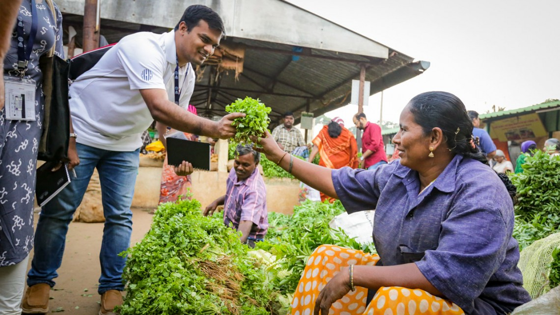 Tanvir Ahmed, left, a Cornell Hubert H. Humphrey Fellow, buys produce at a market in India in January.